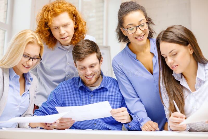 Uśmiechnięta drużyna z papierem przy biurem zdjęcie royalty free