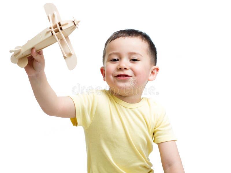 Uśmiechnięta dzieciak chłopiec bawić się drewnianą samolot zabawkę obrazy royalty free