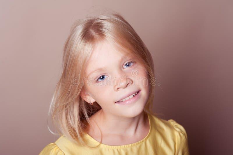 Uśmiechnięta dzieciak dziewczyna na brown zbliżeniu fotografia stock