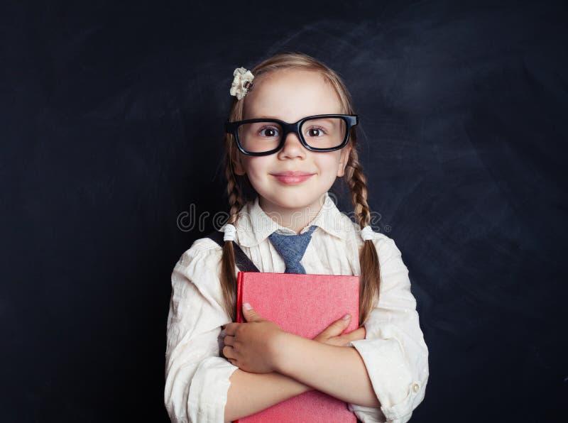 Uśmiechnięta dziecko dziewczyna w mundurku szkolnym odziewa z książką obrazy royalty free