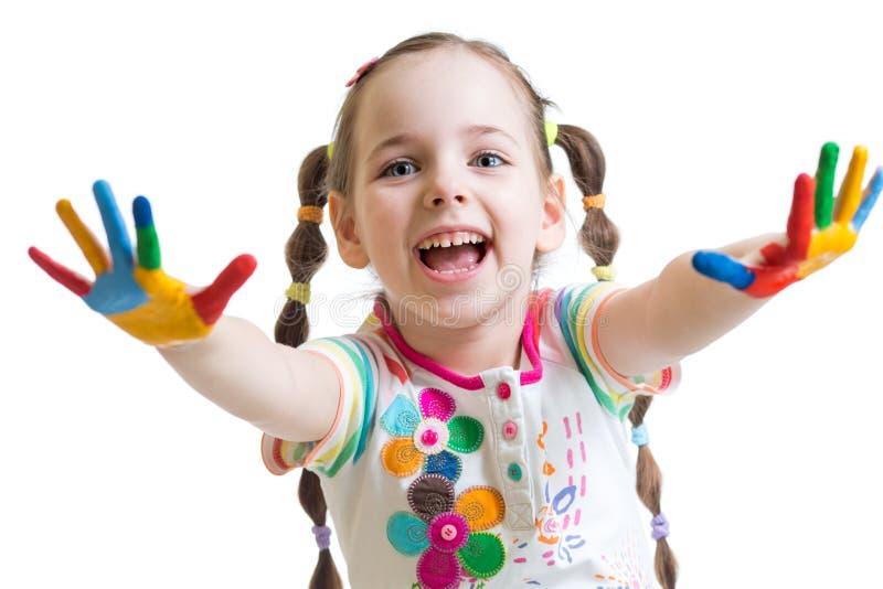Uśmiechnięta dziecko dziewczyna z kolorowymi rękami w farbach obraz stock