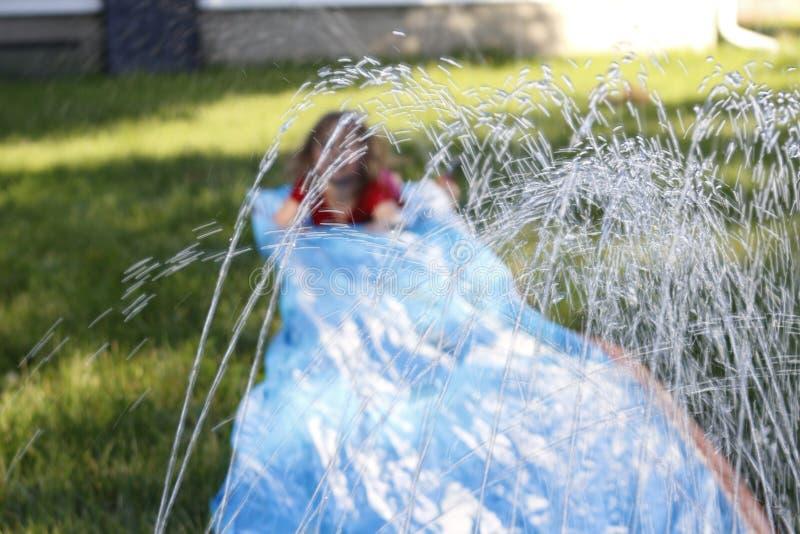Uśmiechnięta dziewczyna ślizga się w dół plenerowego obruszenie i ślizganie selekcyjna ostrość na wodzie przed dzieckiem obraz stock
