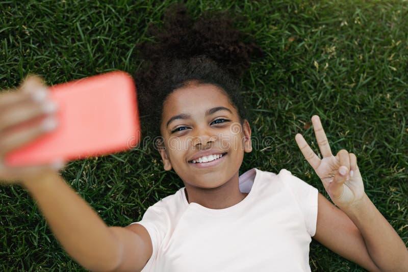 Uśmiechnięta dziewczyna bierze selfie na jej smartphone fotografia royalty free