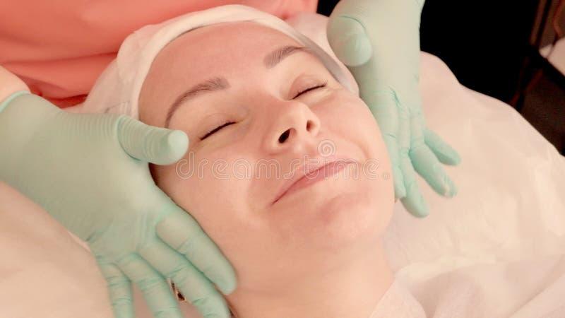 Uśmiechnięta dziewczyna bierze twarzowego masaż w piękno salonie Masażysta ugniata dziewczyna ucho Pi?kno i zdrowie zamkni?ty twa obraz royalty free