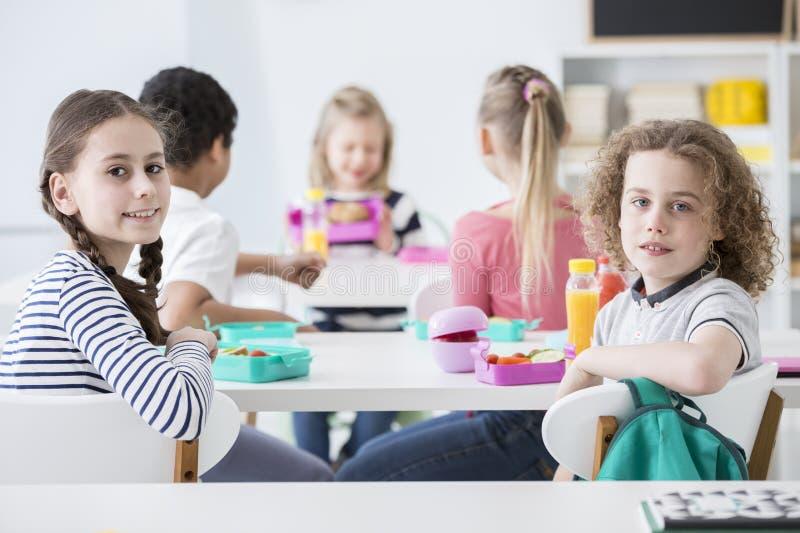 Uśmiechnięta dziewczyna i chłopiec je zdrowego śniadanie obraz stock