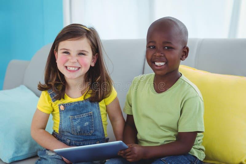 Uśmiechnięta dziewczyna i chłopiec używa pastylkę obraz stock