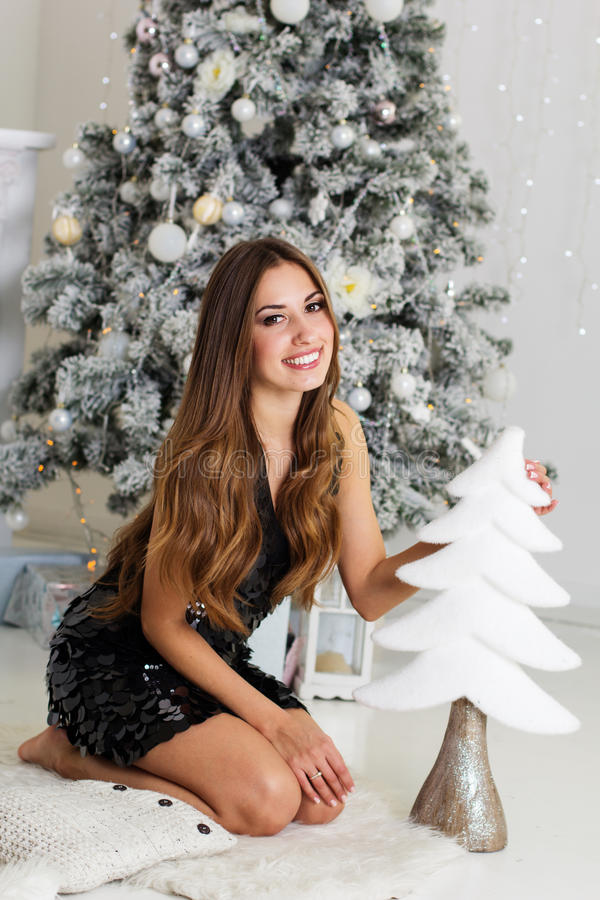 Uśmiechnięta dziewczyna jest siedzącym pobliskim choinką zdjęcie stock