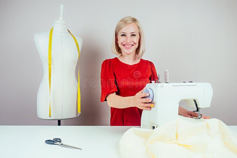 Uśmiechnięta dziewczyna, która pracuje nad maszyną do szycia i manekinem z żółtą taśmą mierniczą na białym tle zdjęcie royalty free