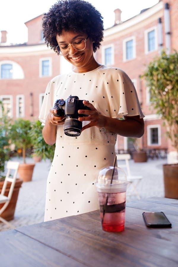 Uśmiechnięta dziewczyna patrzeje na ekranie dslr zdjęcia royalty free