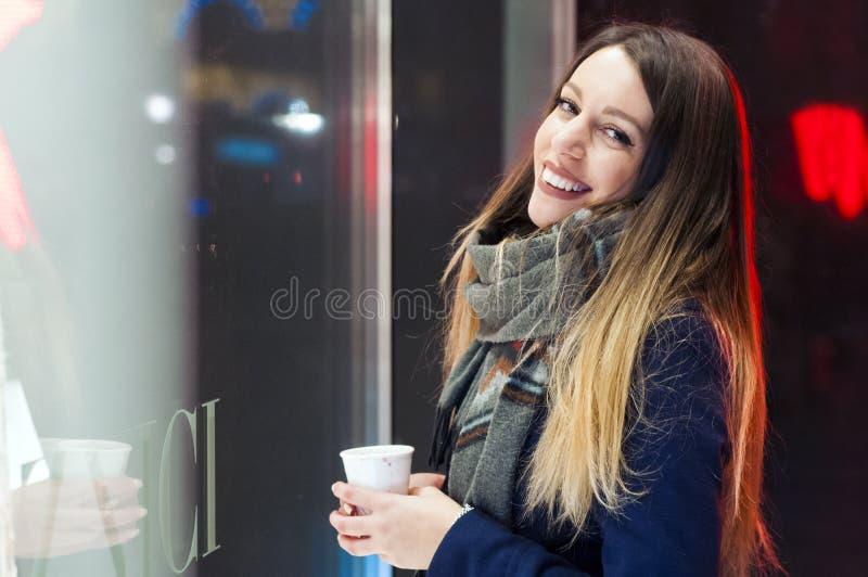 Uśmiechnięta dziewczyna patrzeje sklepowego okno przed wchodzić do Kobiety oon świąteczni boże narodzenia wprowadzać na rynek prz zdjęcie stock