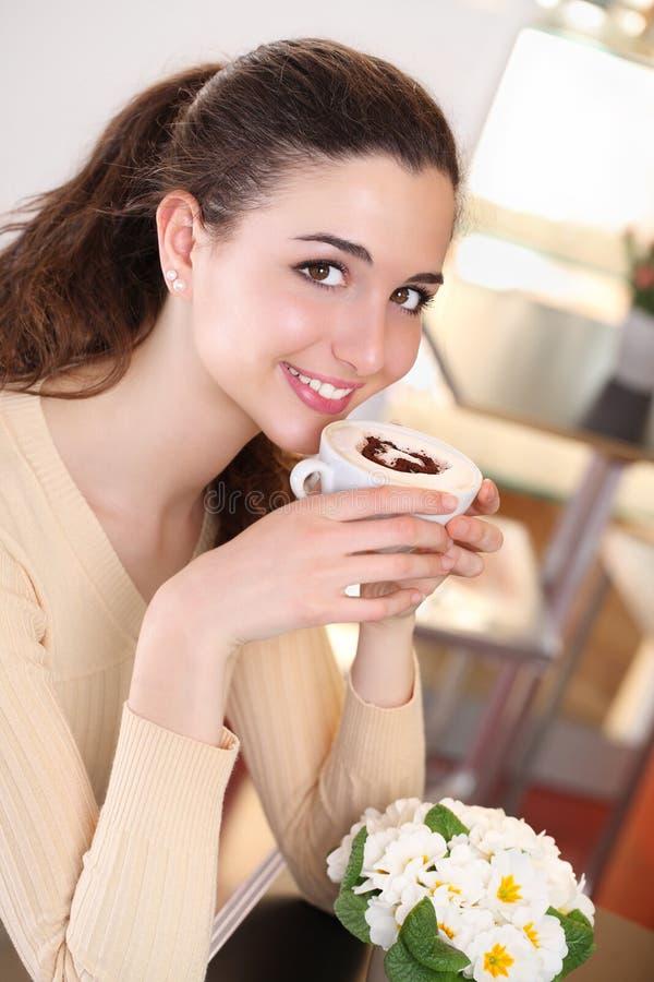 Uśmiechnięta dziewczyna pije filiżankę cappuccino w kawie zdjęcia stock