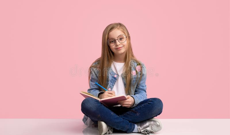 Uśmiechnięta dziewczyna pisze w notatniku obrazy stock