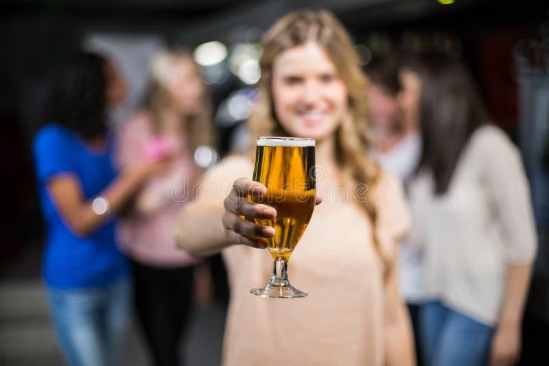 Uśmiechnięta dziewczyna pokazuje piwo z jej przyjaciółmi obraz stock