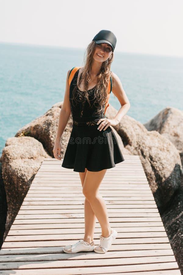 uśmiechnięta dziewczyna pozuje na drewnianym molu przy skałami obraz royalty free
