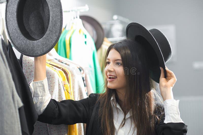 Uśmiechnięta dziewczyna próbuje na czarnych kapeluszach w odzież sklepie zdjęcia royalty free