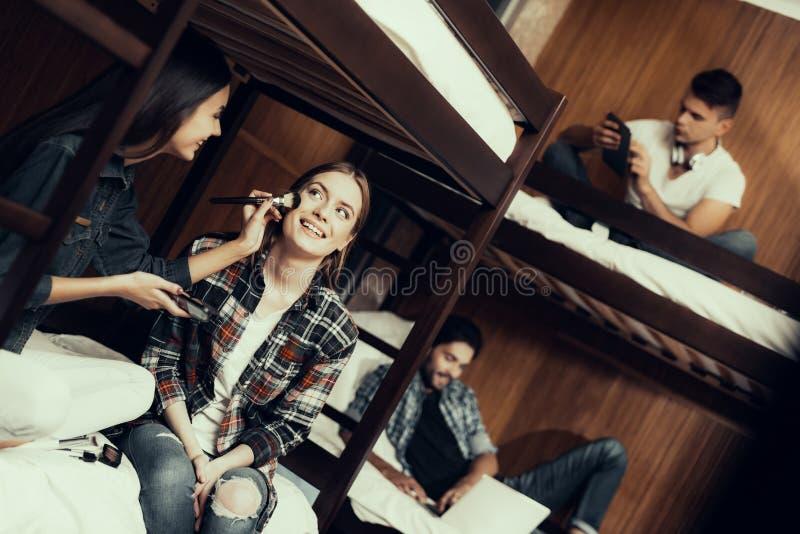 Uśmiechnięta dziewczyna siedzi na łóżku i maluje dziewczyny zdjęcia stock