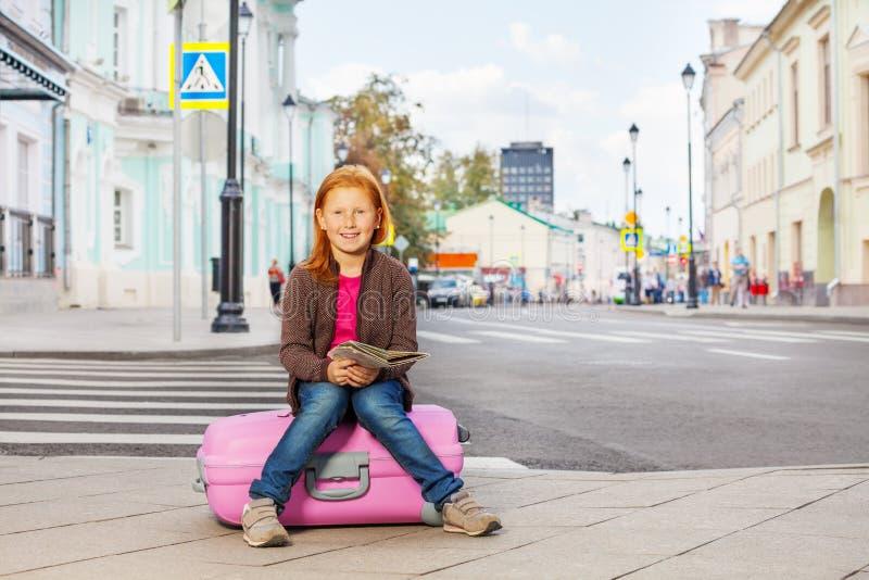 Uśmiechnięta dziewczyna siedzi na różowym bagażu z miasto mapą zdjęcia royalty free
