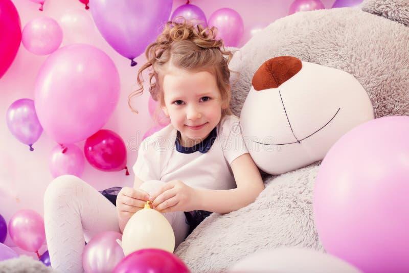 Uśmiechnięta dziewczyna siedzi opierać na dużym misiu obrazy royalty free