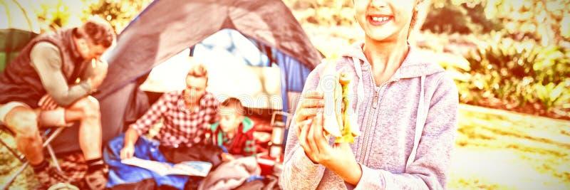 Uśmiechnięta dziewczyna trzyma kanapkę podczas gdy rodzinny obsiadanie na zewnątrz namiotu fotografia stock