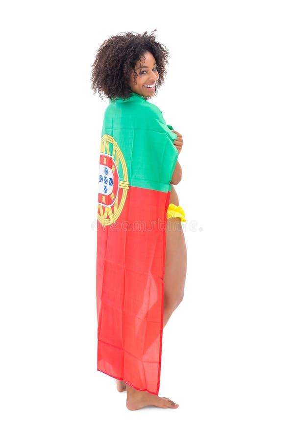 Uśmiechnięta dziewczyna trzyma Portugal flaga nad ramionami w żółtym bikini fotografia royalty free