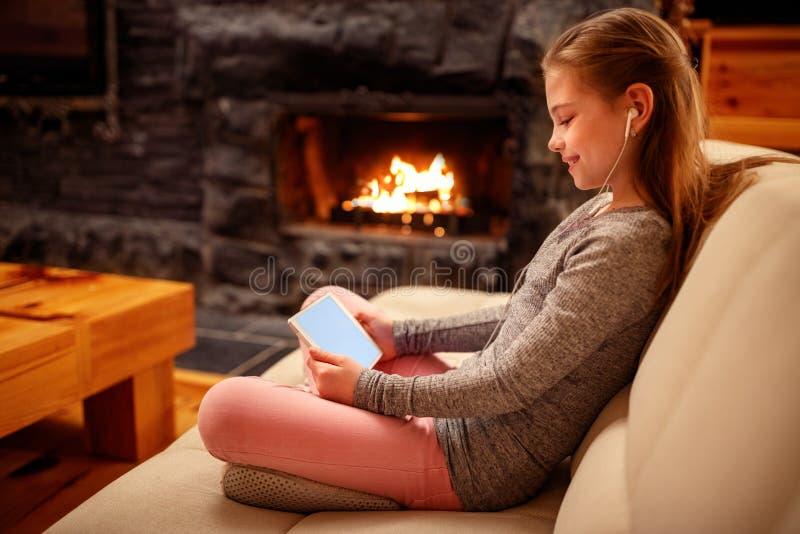 Uśmiechnięta dziewczyna używa iPad cyfrowego komputeru pastylkę na łóżku dla educa obrazy royalty free