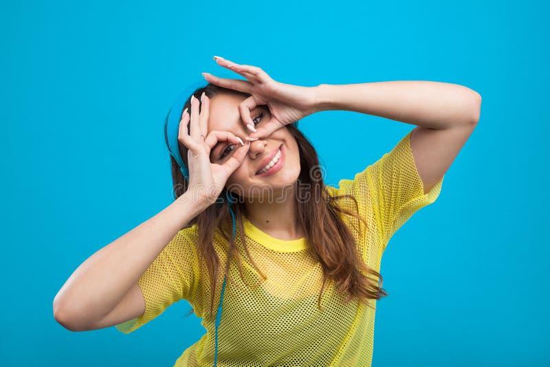 Uśmiechnięta dziewczyna w żółtej koszula robi twarzom zdjęcie royalty free