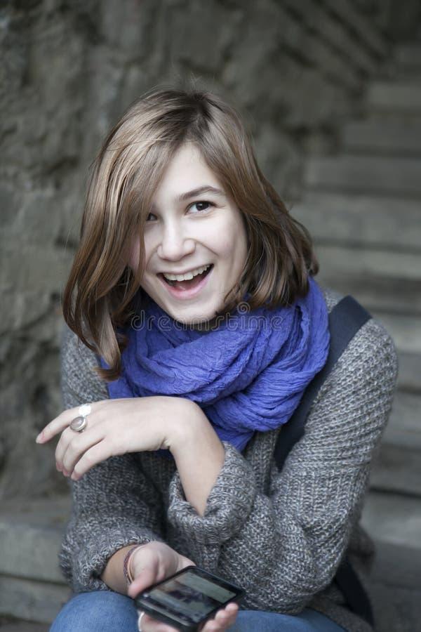 Uśmiechnięta dziewczyna w błękitnym szalika obsiadaniu na kamiennych schodkach zdjęcie royalty free