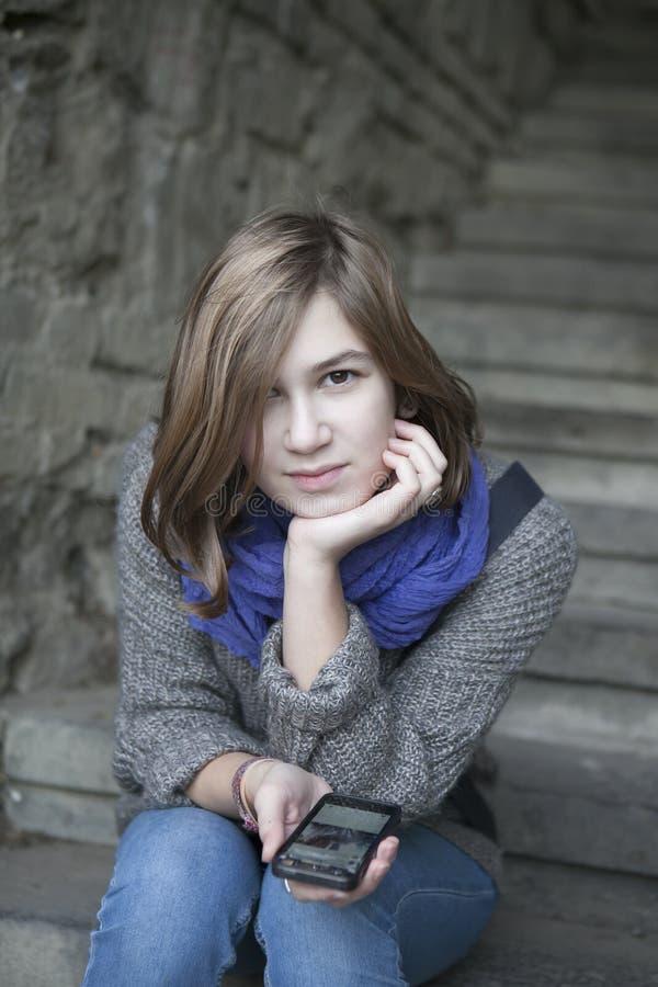 Uśmiechnięta dziewczyna w błękitnym szalika obsiadaniu na kamiennych schodkach outdoors fotografia royalty free