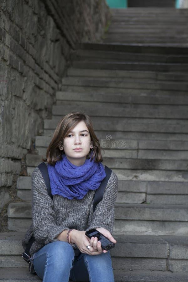Uśmiechnięta dziewczyna w błękitnym szalika obsiadaniu na kamiennych schodkach outdoors fotografia stock