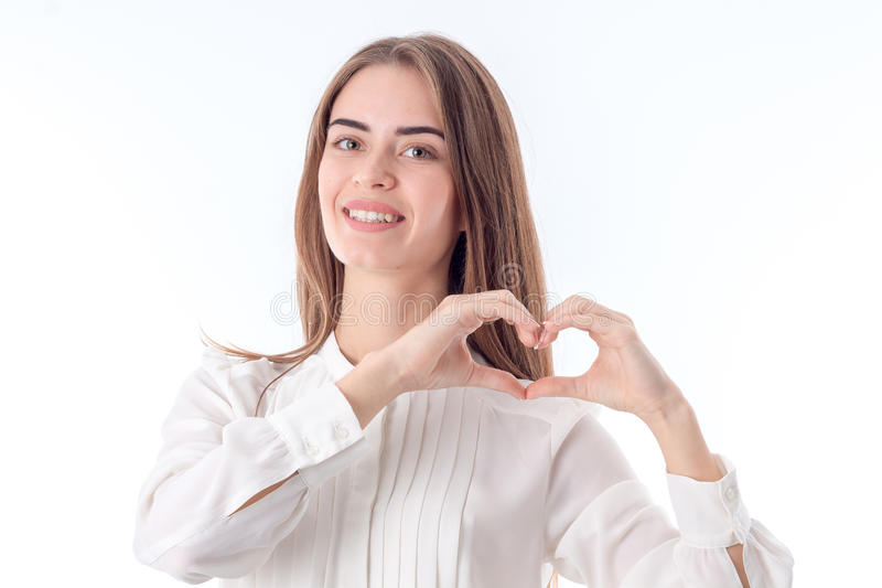 Uśmiechnięta dziewczyna w koszulowych przedstawieniach gestykuluje ręki serce odizolowywającego na białym tle fotografia stock