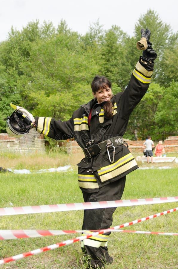 Uśmiechnięta dziewczyna w mundurze strażak przechodzi z hełmem w jej ręce raduje się przeszkoda kurs po tym jak ja pionowo obraz royalty free