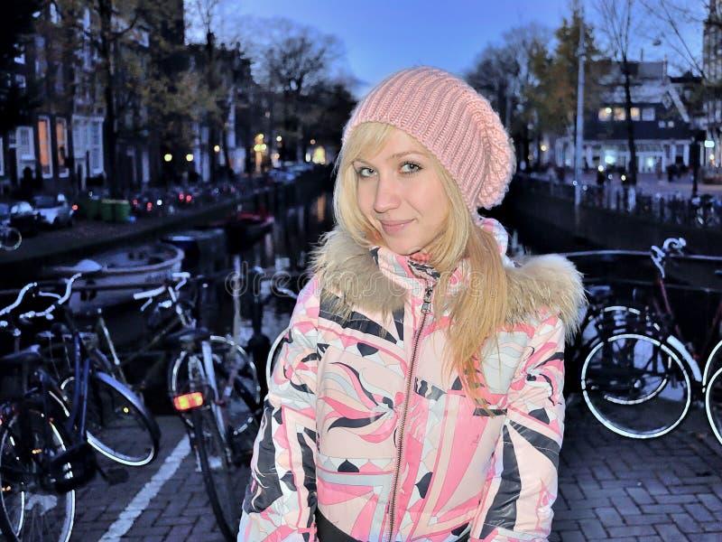 Uśmiechnięta dziewczyna w różowej kurtce blisko kanału Amsterdam na błękitnym godzina wieczór wśród rowerów zdjęcie stock