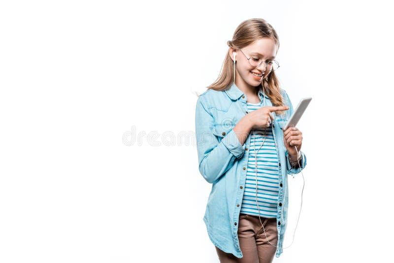 Uśmiechnięta dziewczyna w słuchawkach używać smartphone odizolowywającego na bielu zdjęcia royalty free