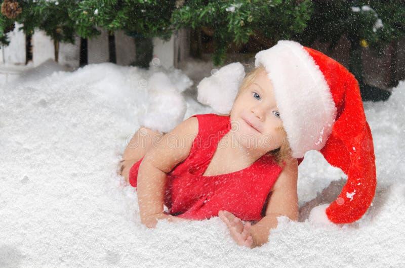 Uśmiechnięta dziewczyna w Santa kostiumu na śniegu fotografia royalty free