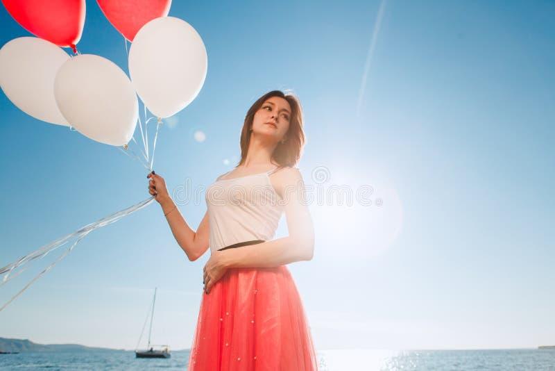 Uśmiechnięta dziewczyna z barwionymi balonami zdjęcia stock