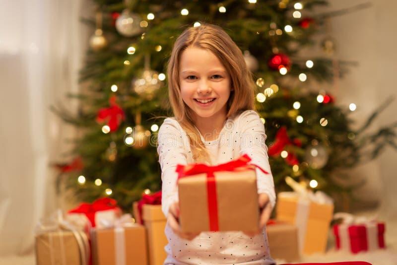Uśmiechnięta dziewczyna z boże narodzenie prezentem w domu zdjęcie royalty free