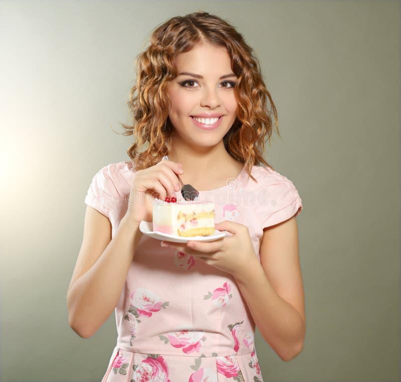 Uśmiechnięta dziewczyna z kawałkiem tort fotografia stock