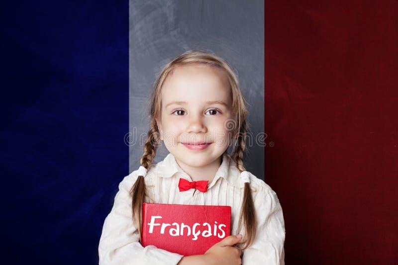 Uśmiechnięta dziewczyna z książką przeciw francuz flaga sztandarowi fotografia stock