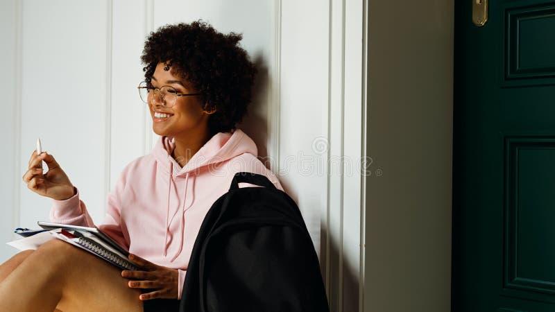 Uśmiechnięta dziewczyna z książkami i cyfrową pastylką na jej kolanach zdjęcia royalty free