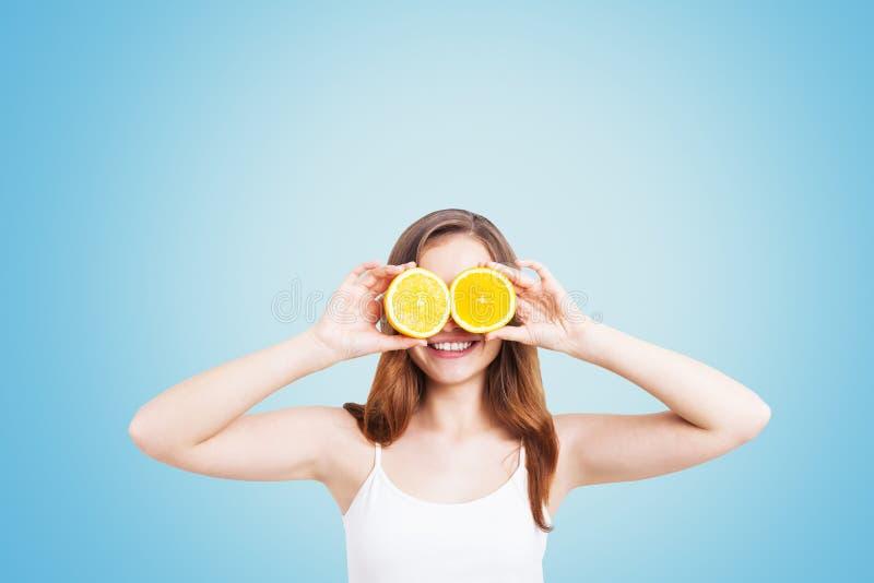 Uśmiechnięta dziewczyna z pomarańczami na błękitnym tle obrazy stock