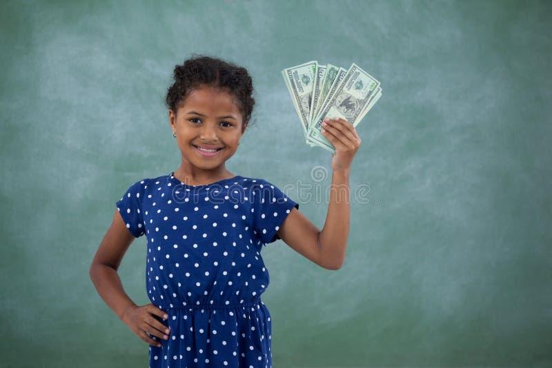 Uśmiechnięta dziewczyna z ręką na biodrze pokazuje papierową walutę fotografia stock