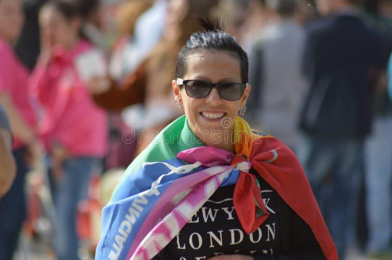 Uśmiechnięta dziewczyna z tęczy flaga na zamazanym tle i ludziach obraz stock