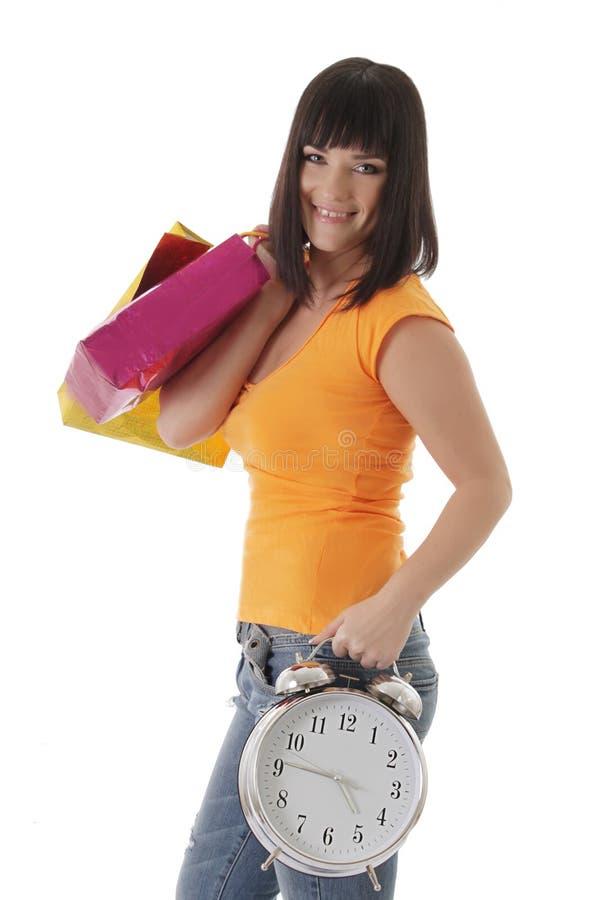 Uśmiechnięta dziewczyna z zakupy błaga i zegar obrazy stock