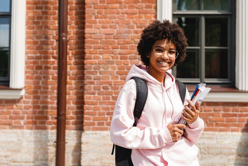 Uśmiechnięta dziewczyny pozycja przy szkołą z książkami obraz royalty free
