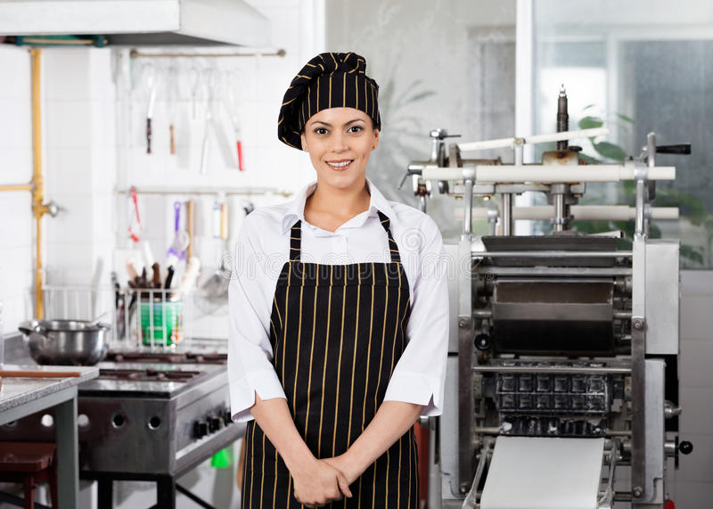 Uśmiechnięta Żeńska szef kuchni pozycja W kuchni obraz royalty free