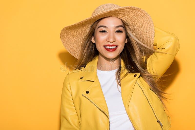 uśmiechnięta elegancka azjatykcia kobieta w słomianym kapeluszu na kolorze żółtym zdjęcie stock