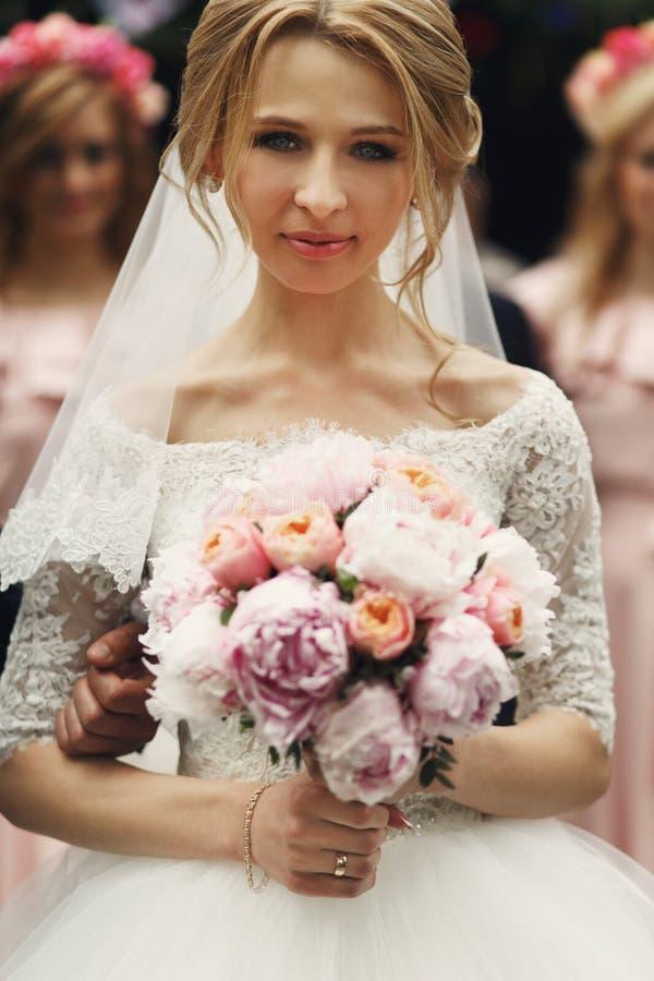 Uśmiechnięta elegancka blondynki panna młoda z różanym ślubnym bukietem w bielu fotografia stock