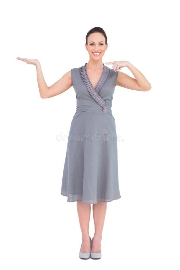 Uśmiechnięta elegancka kobieta w z klasą smokingowym pokazuje kierunku obrazy stock