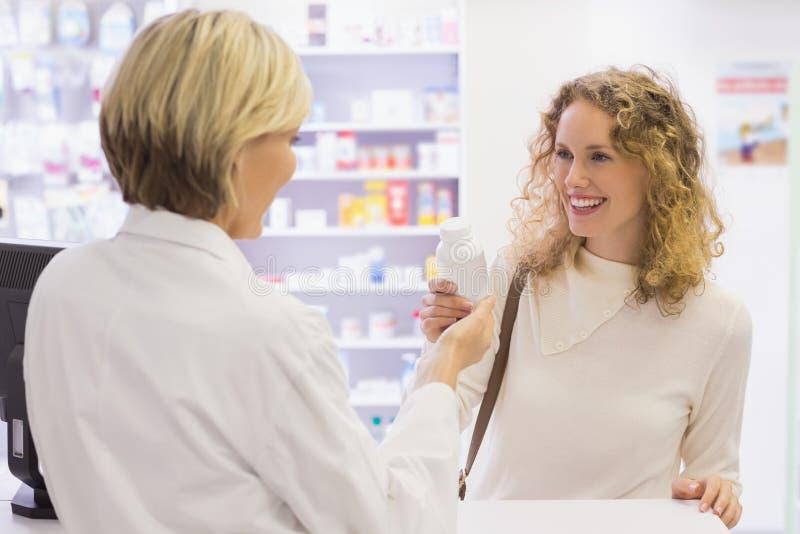 Uśmiechnięta farmaceuta i klient dyskutuje produkt obraz royalty free