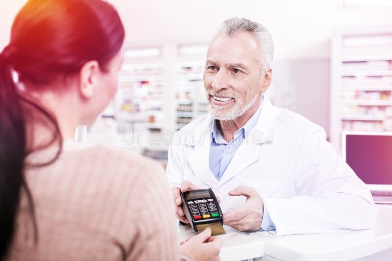 Uśmiechnięta farmaceuta proponuje kobiety zapłata śmiertelnie zdjęcia stock